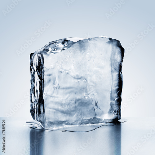 Photo  Cold blue crystal clear frozen block of ice melting to create pool of water on r