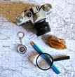 pencil, vintage photo camera, mineral stone, magnifier and compass on old military topographical map