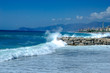 Waves break about a stone pier
