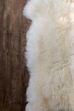 Natural Sheepskin Fluffy Fur Rug On Dark Oak Wooden Floor