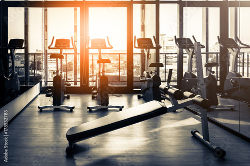 Poster Fitness Elliptical in Modern gym interior with equipment. Row of training exercise bikes wheel detail, backlight. Healthy lifestyle concept