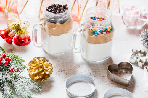 Foto op Aluminium Picknick Christmas homemade gift concept, ingredients for preparation chocolate and rainbow cookies in jar, marshmallow in dish, metallic cutting forms for cookies and decorations on kitchen table