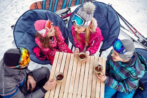 Family enjoying on hot drink at ski resort