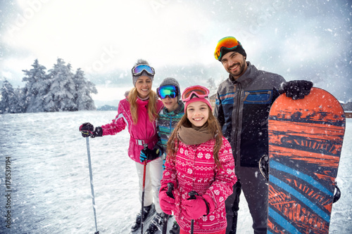obraz dibond family enjoying winter sports and vacation on snow in mountains