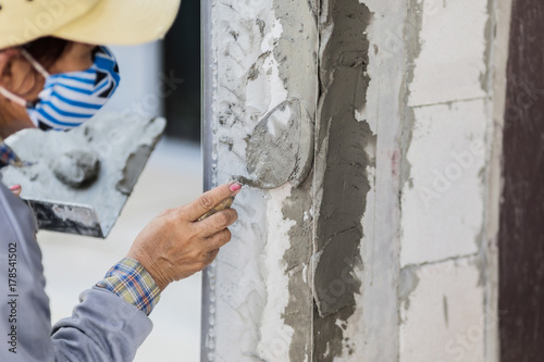 Photo  dirty trowel with glove hand plastering cement mortar in the wall