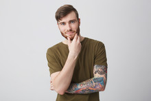 Portrait Of Handsome Cheerful Bearded Ginger Caucasian Male Student With Short Stylish Hairstyle And Tattooed Arm In Brown T-shirt Looking In Camera With Happy And Confident Expression, Holding Hand