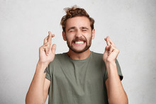 Cheerful Bearded Man Keeps Fingers Crossed, Smiles Broadly And Closes Eyes, Makes Desire Wish. Positive Male Student Believes In Victory Or Success On Exam. Feelings, Attitudes And Reactions