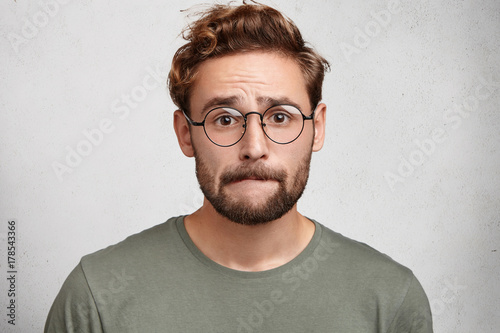 Fotografering  Worried bearded guy in eyewear, bites lower lip, anticipate important decision or feels nervous before doctor`s visit, being afraid of it