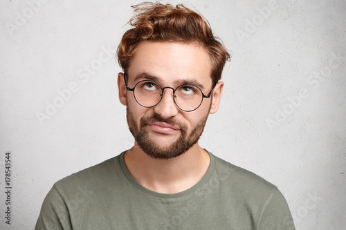 Fotografía  Portrait of stylish bearded man with bored fed up expression, looks displeased up, being tired to explain new material to his friend who can`t understand it