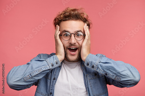 Fotografia  Indoor shot of amazed excited man doesn`t believe his success, keeps hands on head, stares at camera, says omg or wow