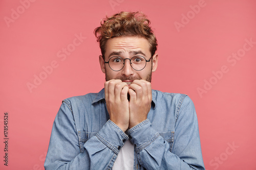 Fotografía  Worried hipster guy bites nails, looks nervous before passing exam or important event in his life