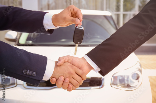 Fototapety, obrazy: Salesman giving car key to customer outdoors