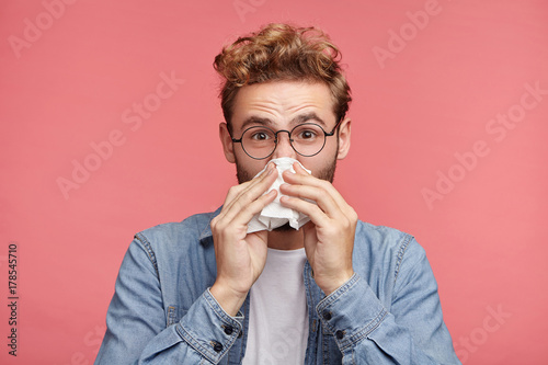 Fotografía  Indoor shot of bearded man has running nose, rubs nose with handkerchief, being ill, caught cold after long walk outdoors on rainy weather
