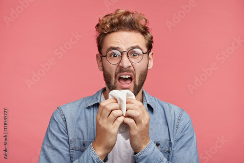 Portrait of ill bearded man sneezes, uses handkerchief, feels unwell, has flu. Sick male has fever or allegic, has tired expression, needs good rest. Unhealthy lifestyle, illness and infection concept
