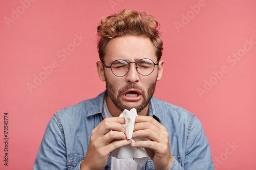 Leinwand Poster  Portrait of ill or sick bearded male sneezes and coughs, uses handkerchief, rubs nose, being allergic to animals