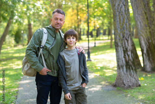 Portrait of father with his son walking together in autumn park. Family leisure. Parenting. Parenthood.