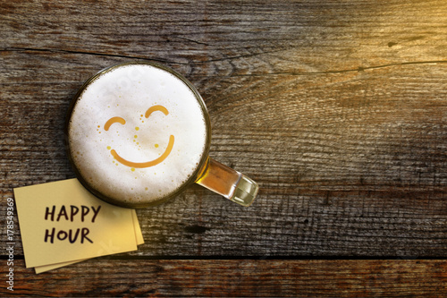 Foto auf Leinwand Bier / Apfelwein Happy Hour Concept for Bar, Cafe or Night club to Promote an Offer, Smiley Face on Foam in Glass of Beer over Wooden Table, Top View