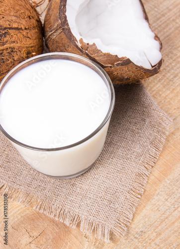 Fototapeta Kokos z kokosowym mlekiem na drewnianym tle.