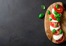 Sliced Tomatoes And Mozzarella On A Wooden Board Made Of Olive Tree, Dark Stone Background. Top View, Copyspace