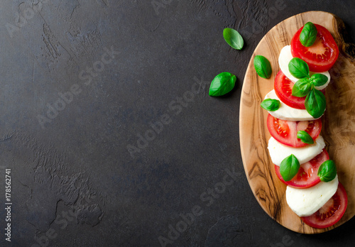 Fotografía Sliced tomatoes and mozzarella on a wooden board made of olive tree, dark stone background