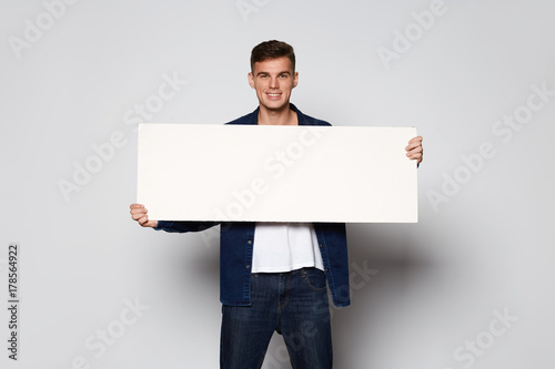 Casual Man holding white papper card on white background at studio