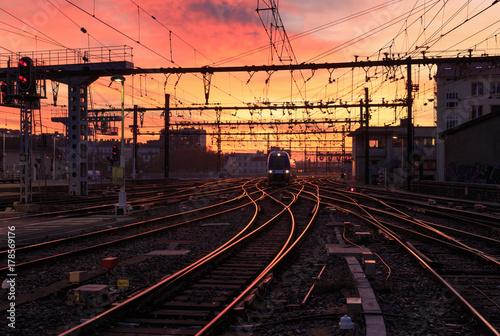 Poster Voies ferrées A train on the railroad tracks during sunrise. Gare de Lyon-Perrache, Lyon, France.