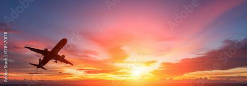 Fototapeta premium Sylwetka samolotu pasażerskiego latającego w zachodzie słońca.