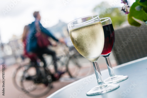 Poster de jardin Bar Glasses of white and red wine on a table outside a bar in Amsterdam
