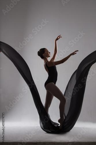 Foto Feminine with arms raised ballerina dancing on black fabric in b
