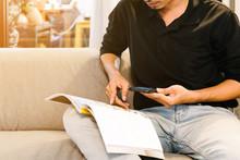 Asian Man Reading A Magazine A...