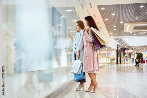 Leinwand Poster Full length portrait of two beautiful girls  in shopping center looking at windo