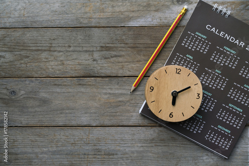 Obraz close up of clock, calendar and pencil on the table, planning for business meeting or travel planning concept - fototapety do salonu