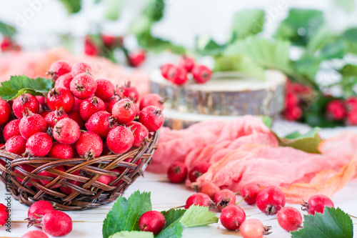 Obraz na płótnie Berries and leaves of hawthorn in a wicker basket on a wooden table