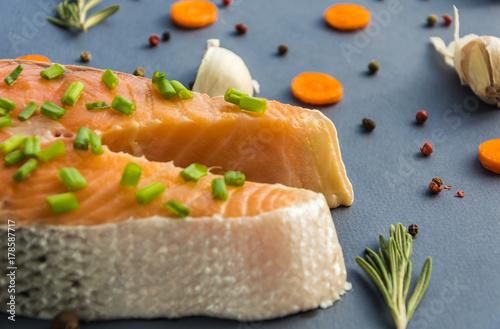 Fototapeta Surowy łosoś z rozmarynem przypraw, grochu z czarnego pieprzu, kawałkiem czosnku i marchwi