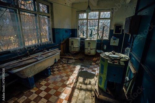 Sinister and creepy old laundry room with a dirty floor and