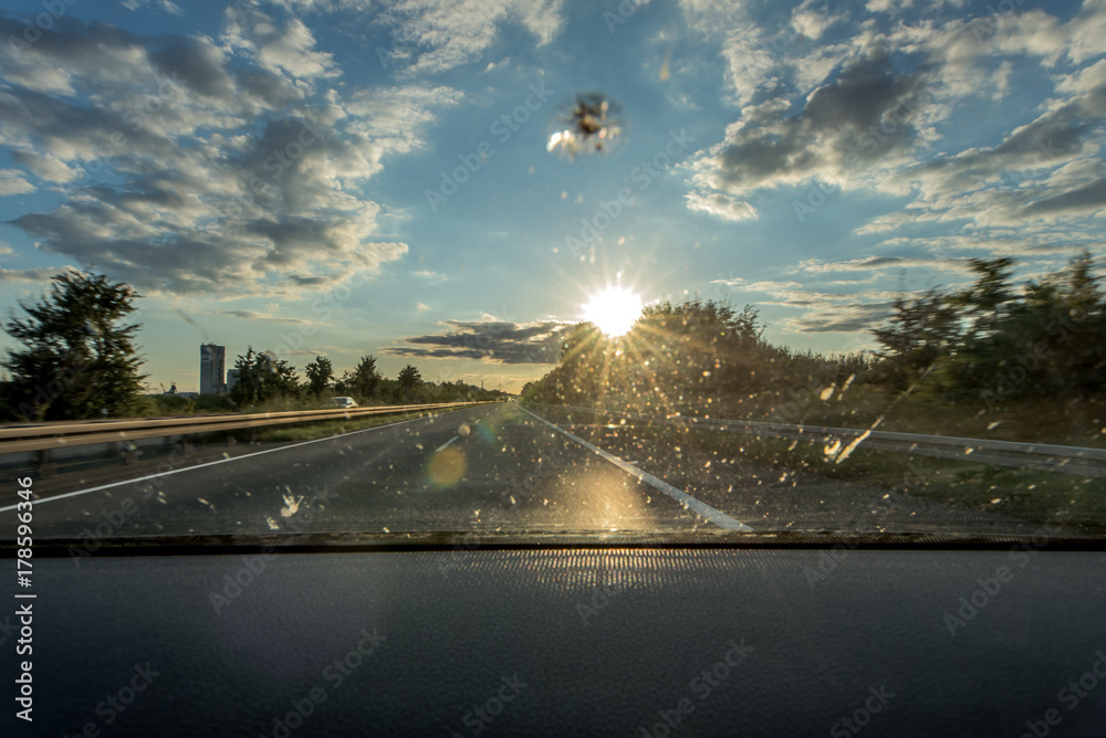 Fotografie, Tablou  Dirt on the windshield of a vehicle, a stone chase and backlight lead to poor vi