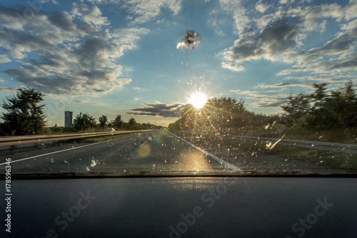 Fotografie, Obraz Dirt on the windshield of a vehicle, a stone chase and backlight lead to poor vi