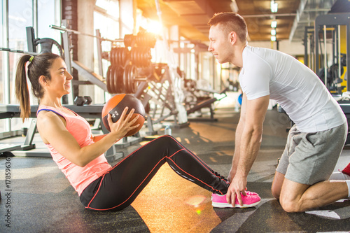 Fotografie, Obraz  Sporty girl doing crunches with fitness ball with assistance of her fitness instructor in gym