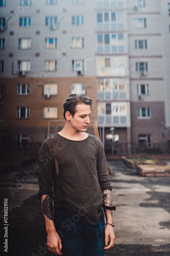 Fototapety, obrazy: Guy with tattoos smokes cigarettes on the street, walks in the city on the street among high-rise buildings
