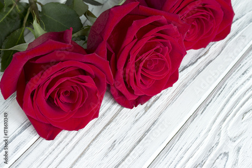 three-red-roses-on-white-wooden