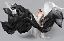 Fashion Portrait Of A Beautiful Woman In A White And Black Dress. The Fabric Flies In The Wind.