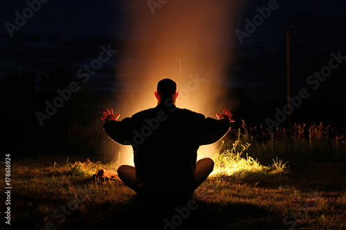Fotografía A bearded man sits by the fire holding out his hands to the fire