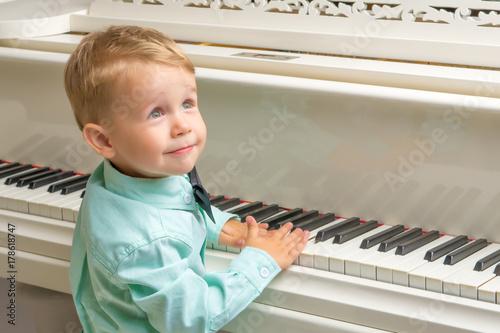 Plakat Mały chłopiec gra na pianinie