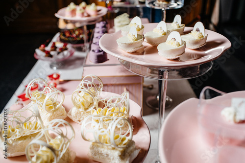 Poster Dairy products Wedding reception dessert table with delicious decorated white cupcakes with frosting closeup