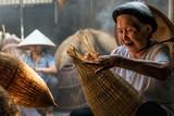 Stary Wietnamski żeński rzemieślnik robi tradycyjnemu bambusowej ryba oklepu lub wyplata przy starym tradycyjnym domem w Thu sy handlu wiosce, Wieszający jen, Wietnam, tradycyjny artysty pojęcie - 178627979