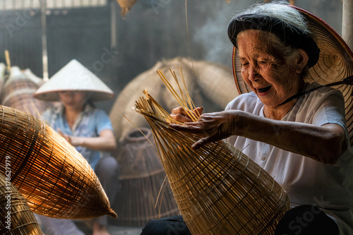 Fotografia  Old Vietnamese female craftsman making the traditional bamboo fish trap or weave