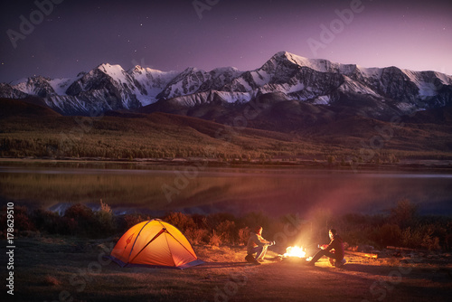Two men tourists sitting at the illuminated tent near campfire