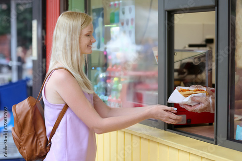 Young woman buying food in street kiosk