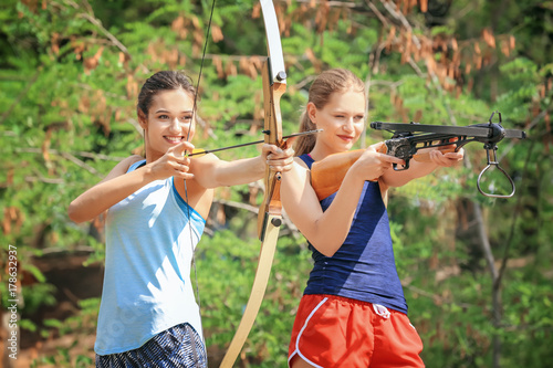 Photographie Young women shooting bow and crossbow outdoors