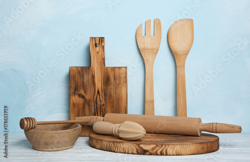 Fotomural  Wooden kitchen utensils on table against blue wall